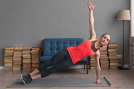 Fitness woman doing side plank exercise on mat at home