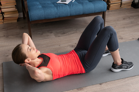 Fitness woman doing abs crunch workout on floor at home