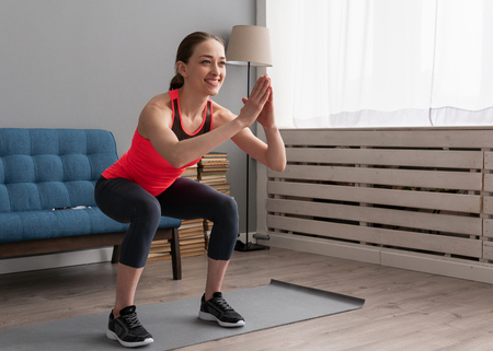 Happy fitness woman doing squat exercise at home Standard-Bild