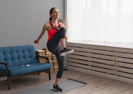 Vrouw doet fitnesstraining thuis en loopt op hoge knieën