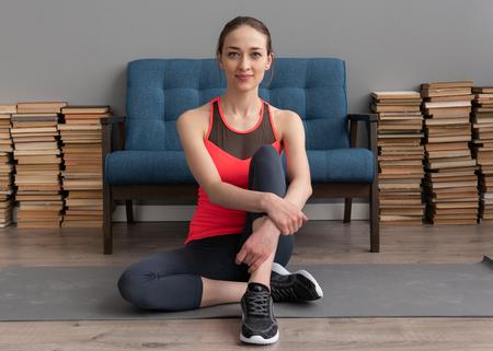 Fitness woman sitting on floor at home Standard-Bild