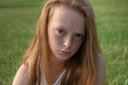 Sad little girl looking in camera with unhappy eyes Standard-Bild