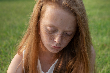 Gloomy face of sad little girl with freckles with lowered eyes Stock Photo