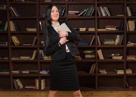 Attractive woman holding book and smiling near bookshelf
