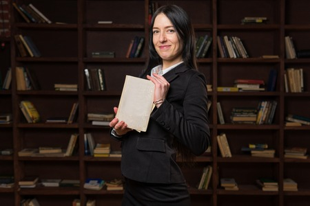 Happy woman holding book near bookshelf in library