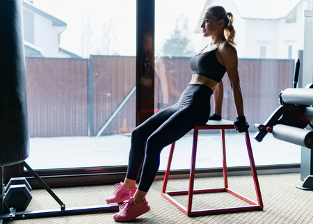 Fitness woman with perfect slim and muscular body posing in gym near window Standard-Bild