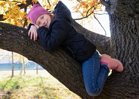 Happy little girl sitting on branch of big and smiling on sunny autumn day