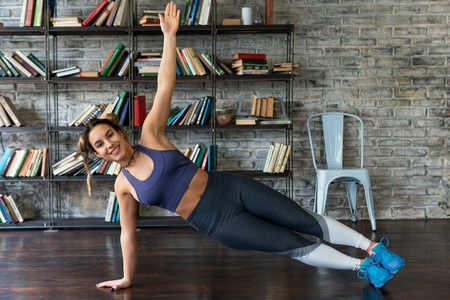 Young happy fitness woman doing side plank exercise during yoga at home