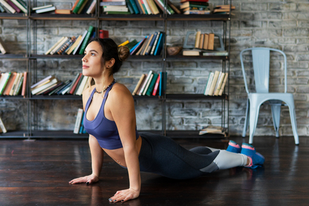 Fitness woman doing cobra pose during yoga workout on floor at home