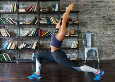 Fitness woman doing front lunge during yoga exercise at home