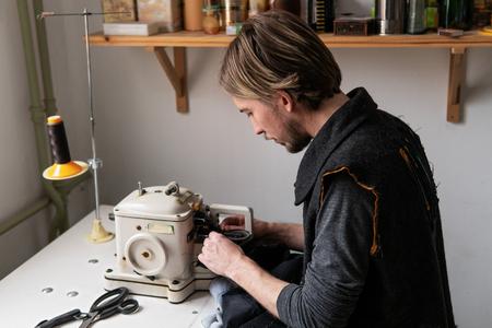 Man tailor working on furrier machine in workshop Standard-Bild