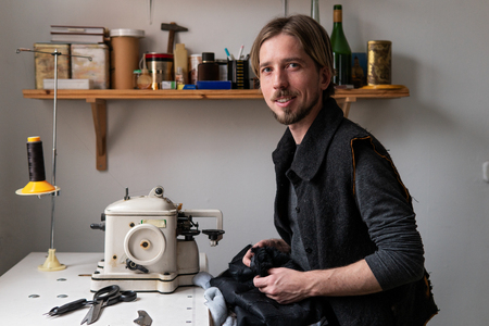 Young man tailor smiling at workplace in sewing workshop Archivio Fotografico