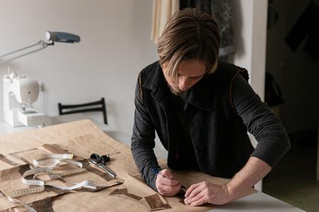 Man tailor making clothing pattern while work in workshop