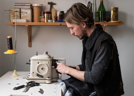 Handsome man tailor sew fur on furrier machine in workshop Standard-Bild
