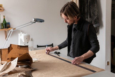 Young creative man tailor draws clothing pattern in workshop