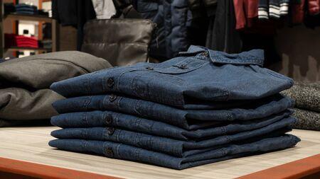 Blue denim shirts on table in clothing store Standard-Bild