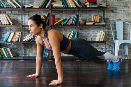 Woman doing push ups workout during fitness training on floor at home Standard-Bild