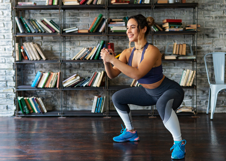Woman doing squat workout and smiling during fitness training at home