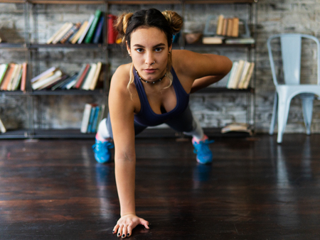 Young fitness woman doing push ups exercise on one hand on floor
