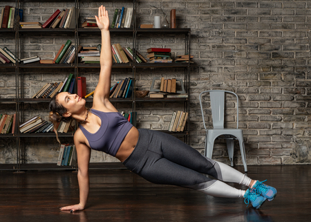 Fitness woman doing side plank during yoga workout at home