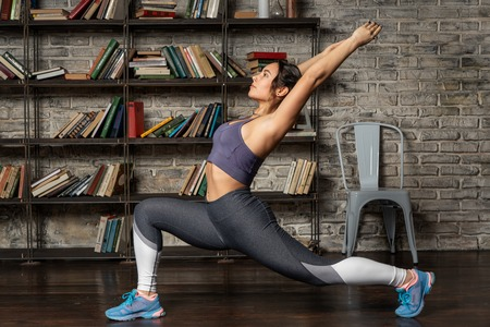 Young fitness woman doing front lunge during yoga exercise