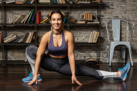 Young happy fitness woman doing leg stretching exercise