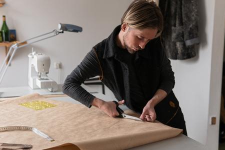 Male fashion designer with scissors cuts paper clothing pattern in workshop Standard-Bild
