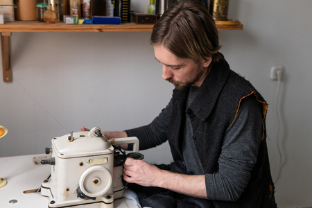Young male tailor sewing fur on furrier machine