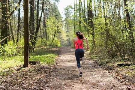 Female runner run in spring sunny forest