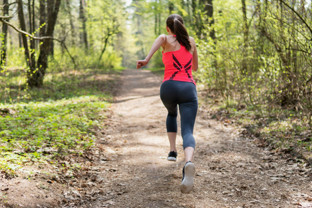 Active woman running in spring sunny forest Archivio Fotografico