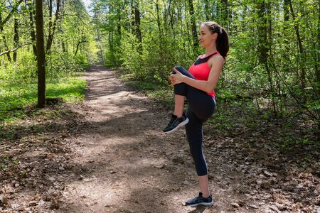 Woman runner doing warm-up exercise before jogging in forest