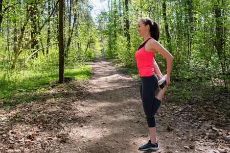 Fitness woman doing leg stretching before run in forest