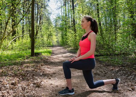 Fitness woman doing front lunge before run in summer forest