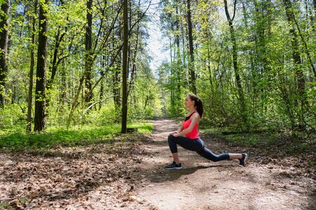 Fitness woman doing leg stretching in summer forest