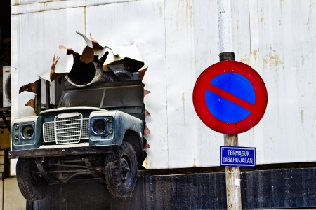 KUALA LUMPUR, MALAYSIA - SEPTEMBER 24: An old vehicle is breaking through a wall as store front decoration in Kuala Lumpur on September 24, 2010. Kuala Lumpur is a modern city popular for shopping.