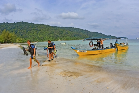 dive trip: KUALA BESUT, MALAYSIA  - MAY 18  Scuba Divers walking on beach after a dive trip in Perhentian Islands on May 18, 2006  Perhentian Islands is a popular destination for new divers  Editorial