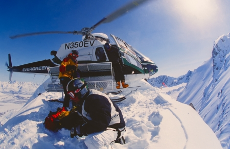 VALDEZ, ALASKA - APRIL 22: Snowboarder Esben Pedersen being dropped of by helicopter on an isolated peak in the Chugach Mountains on April, 22, 2002. Valdez is the hub for Heli-skiing in Alaska.