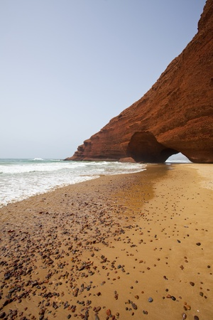 eroded: Arch rock formation on the beach. Morocco.  Stock Photo