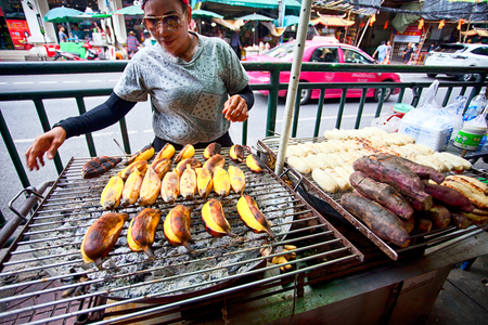 BANGKOK, THAILAND - JULY 30, 2017: Unknown vendor preparing food at a street side restaurant. More than 16.000 people are registered as street vendors in Thailand