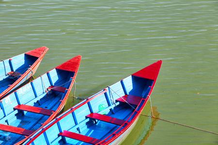 Small wooden boats on the Phewa Lake in Pokhara, Nepal