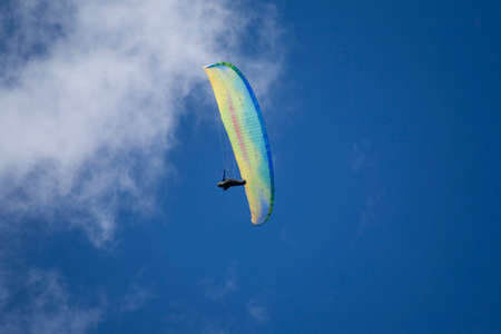 A sportsman paragliding high in the blue sky.
