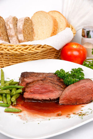 Steak in red wine with a side dish of asparagus on a white plate Stock Photo