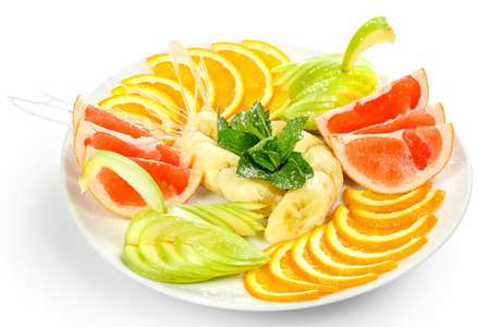 Oranges, apples, grapefruit, banana cut into slices with fresh mint leaves and caramel on a white plate Stock Photo