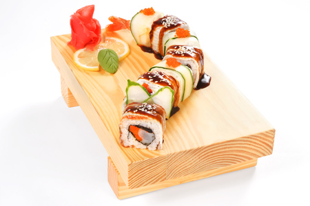 prepared: Set of Dragon of eight rolls with eel, caviar of flying fish, crab meat, cucumber and sesame, decorated with wasabi, marinated ginger and lemon on a wooden stand in a white background Stock Photo