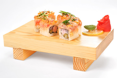 A set of eight fried rolls with ham, bacon, pickled onion, pickled cucumber and hard fused cheese, decorated with wasabi, fresh cucumber, marinated ginger and lemon on a wooden stand in a white background