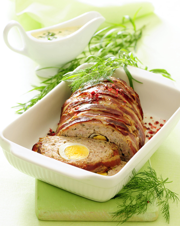 Baked meatloaf with egg stuffing and tarragon sauce. Stock Photo
