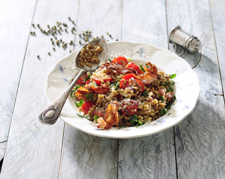 Pearl barley, pork and tomato risotto. Stock Photo