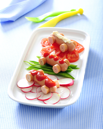 Mini hot dog cars and fresh veggies for funny lunch for kids