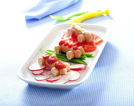 Mini hot dog cars and fresh veggies for funny lunch for kids.