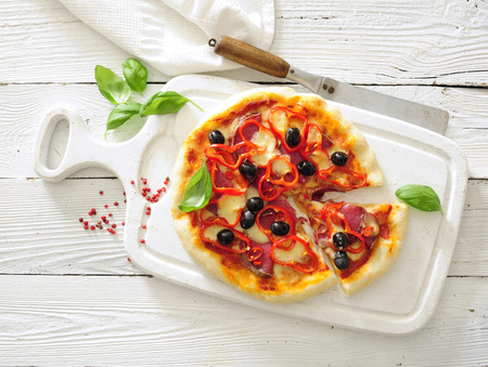 Fresh pizza topped with salami, mozzarella, red peper and black olives.